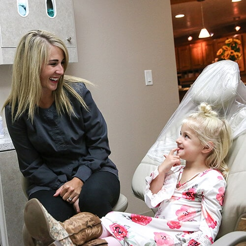 One of our dental assistants talking to a little girl who is wearing a white dress with red roses