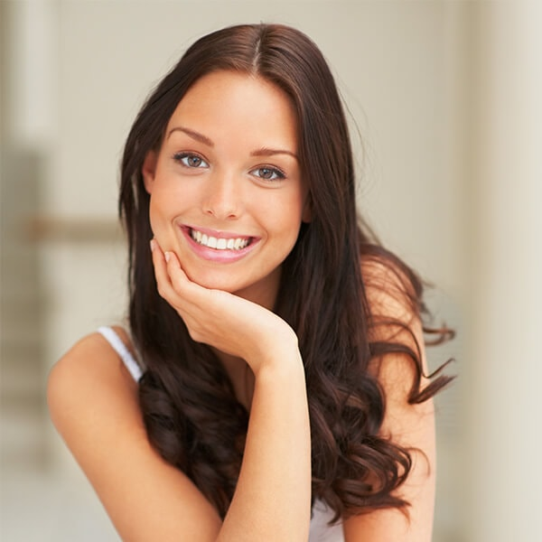 A young woman with long brown hair smiling while placing her right hand under her chin