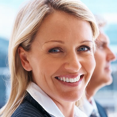 A blonde woman dressed in office attire and smiling