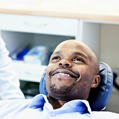 A male patient receiving restorative dentistry while in the dentist's chair
