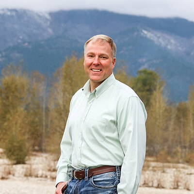 Our dentist in Hamilton, MT, Dr. Justin Simmons, smiling while standing front of mountains
