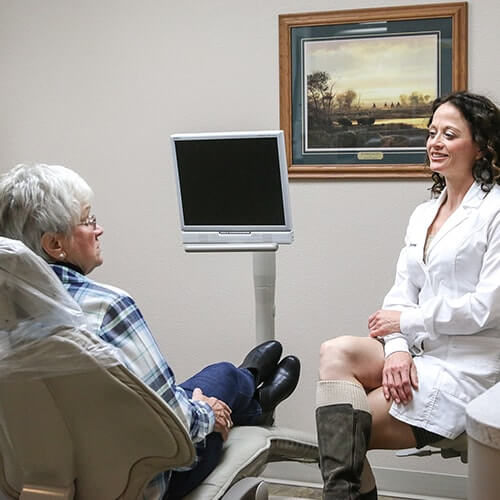 Our dentist in Hamilton, MT, Dr. Stacey Gividen inside the dental office talking to an elderly woman