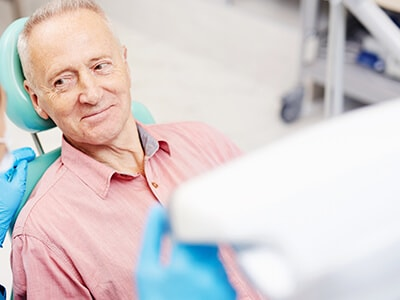An older male patient wearing a pink shirt and sat in the dentist chair