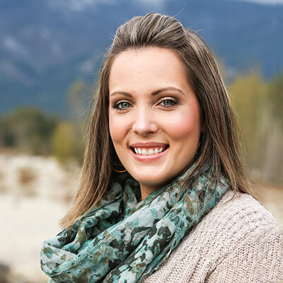 A team member smiling while wearing a long scarf and standing front of mountains