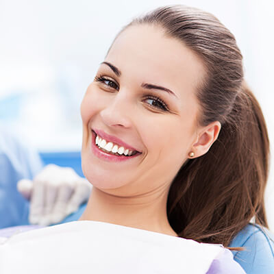 A smiling woman sitting in the dentist's chair, ready for restorative dentistry