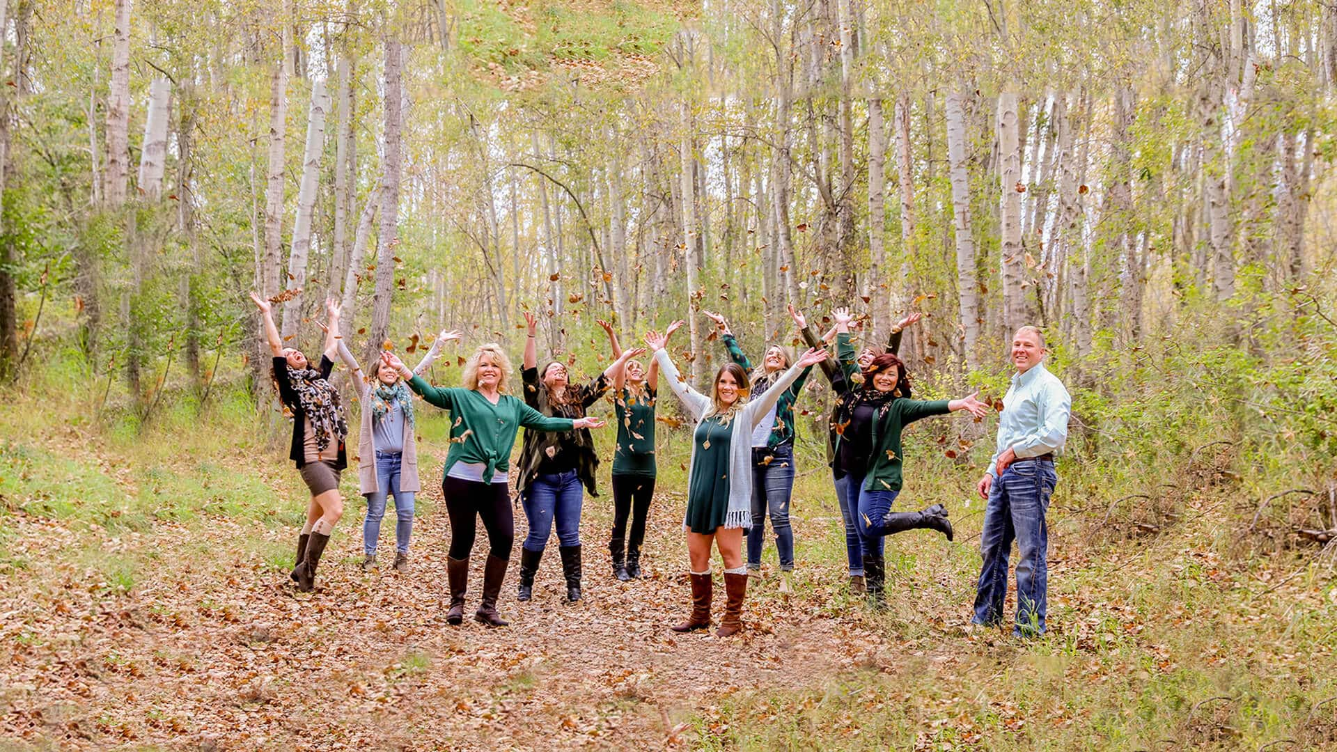 Our dentist in Hamilton, MT, and our team in a forest and throwing leaves