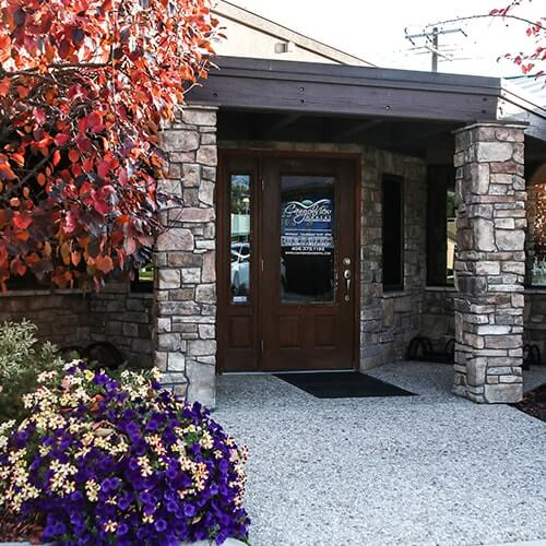 The entrance to our office with purple and red flowers around it
