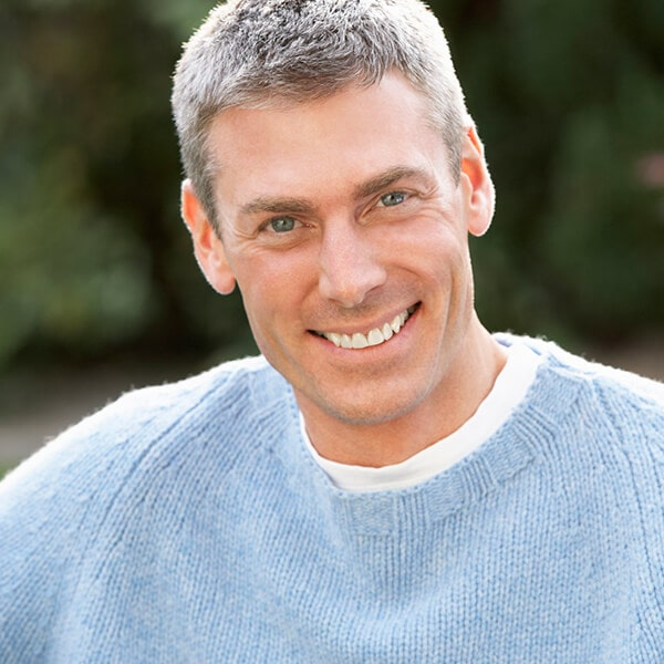 A mature man with short hair smiling in the park, he wears a blue sweater