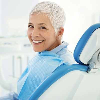 A mature woman with blue shirt sitting on the dentist's chair while smiling