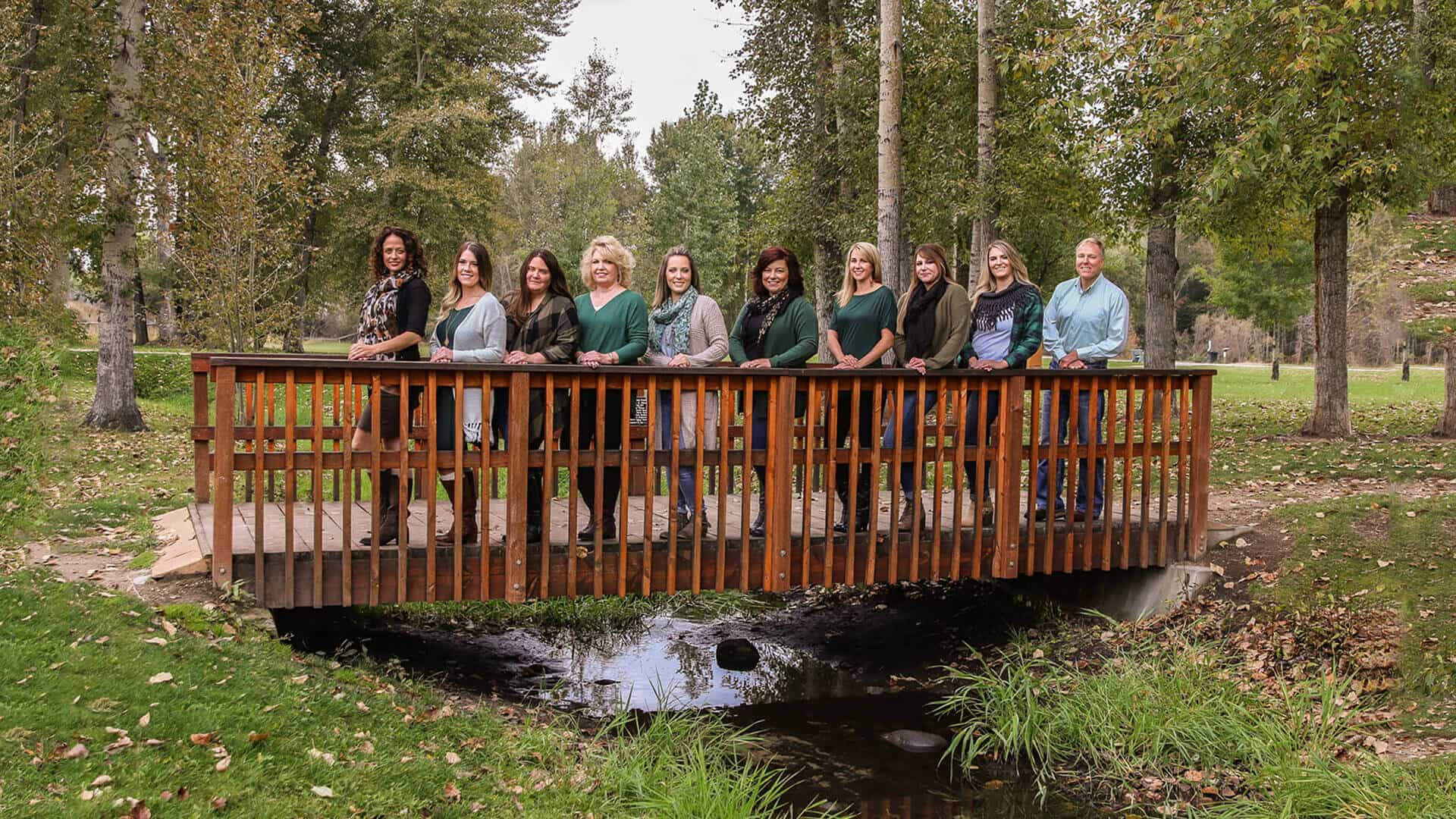 Our Canyon View Dental team standing on a wooden bridge and smiling