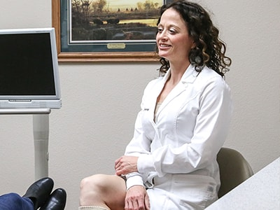 Dr. Stacy Gividen inside the dental office sitting next to a monitor