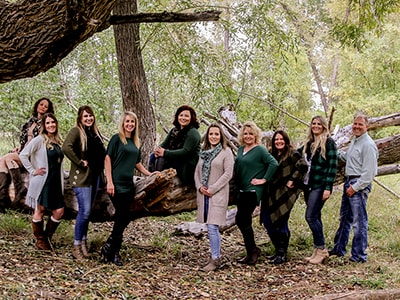 The entire Canyon View Dental team standing next to a fallen tree