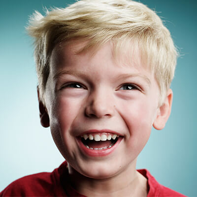 A blond boy with red shirt smiling at his family dentistry appointment