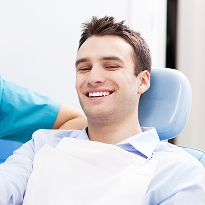 A young man with blue shirt and black hair sitting in the chair ready for family dentistry