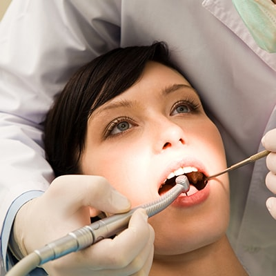 A dentist performing family dentistry on a female patient with modern instruments