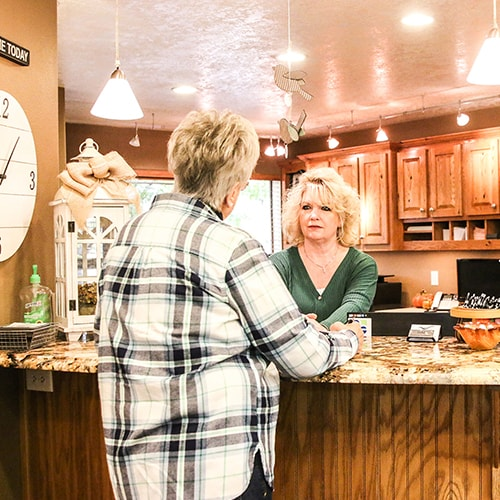 An older woman talking to a member of our team in the reception area